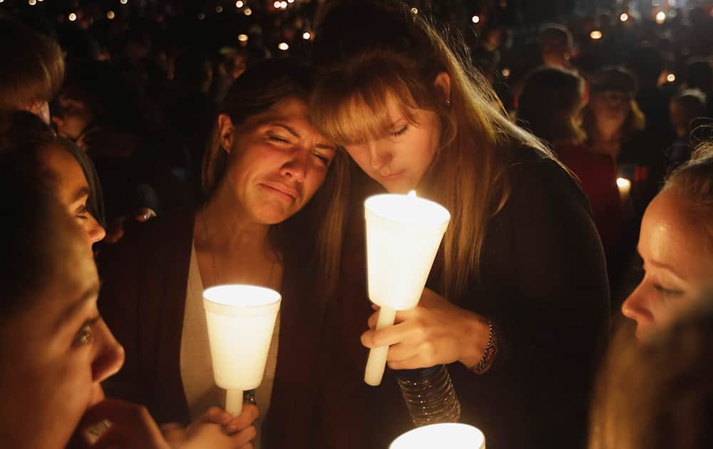Kristen Sterner, left, and Carrissa Welding, both students of Umpqua Community College, embrace each other during a candle light vigil for those killed during a fatal shooting at the college.