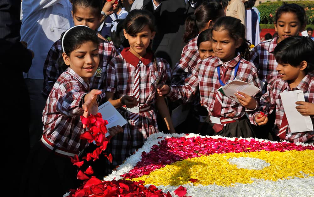 Children offer floral tributes at the memorial of Mahatma Gandhi on the occasion of his birth anniversary, in New Delhi.