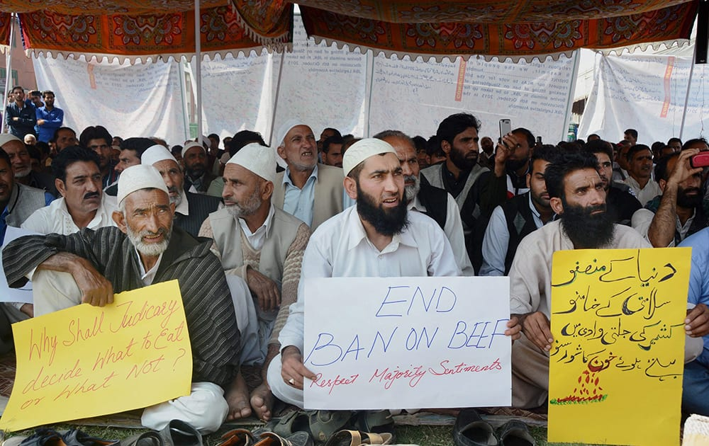 A group of people shout slogans holding placards during a protest against Beef ban by J&K High Court, in Srinagar.