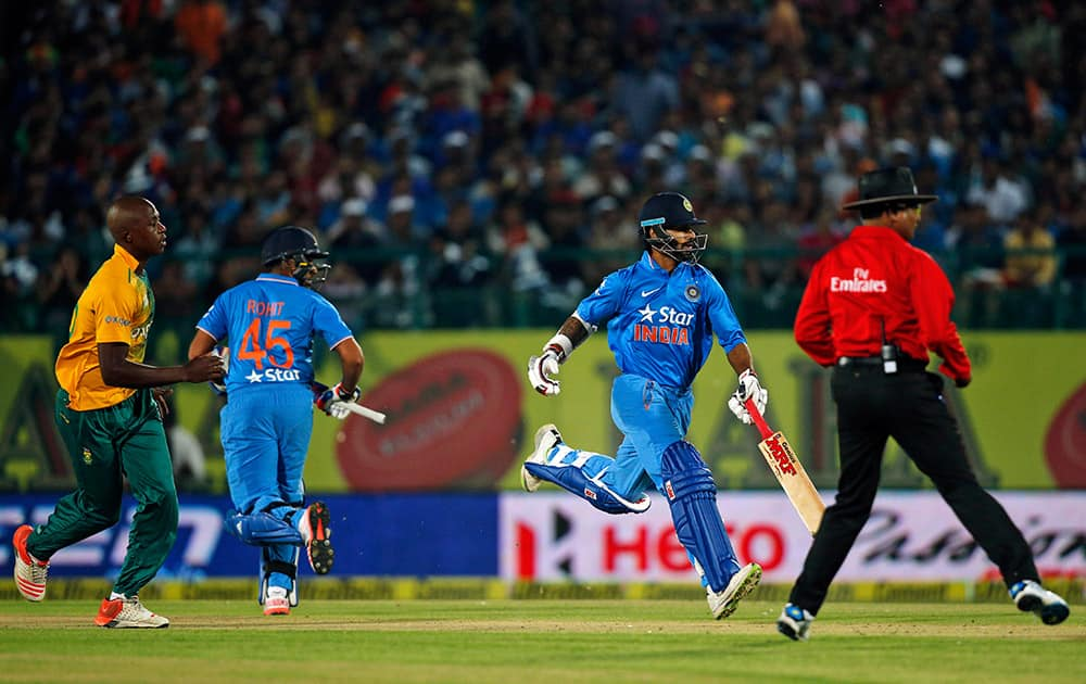 Virat Kohli, second right, and Rohit Sharma run between the wickets during the first Twenty20 cricket match against South Africa in Dharmsala.