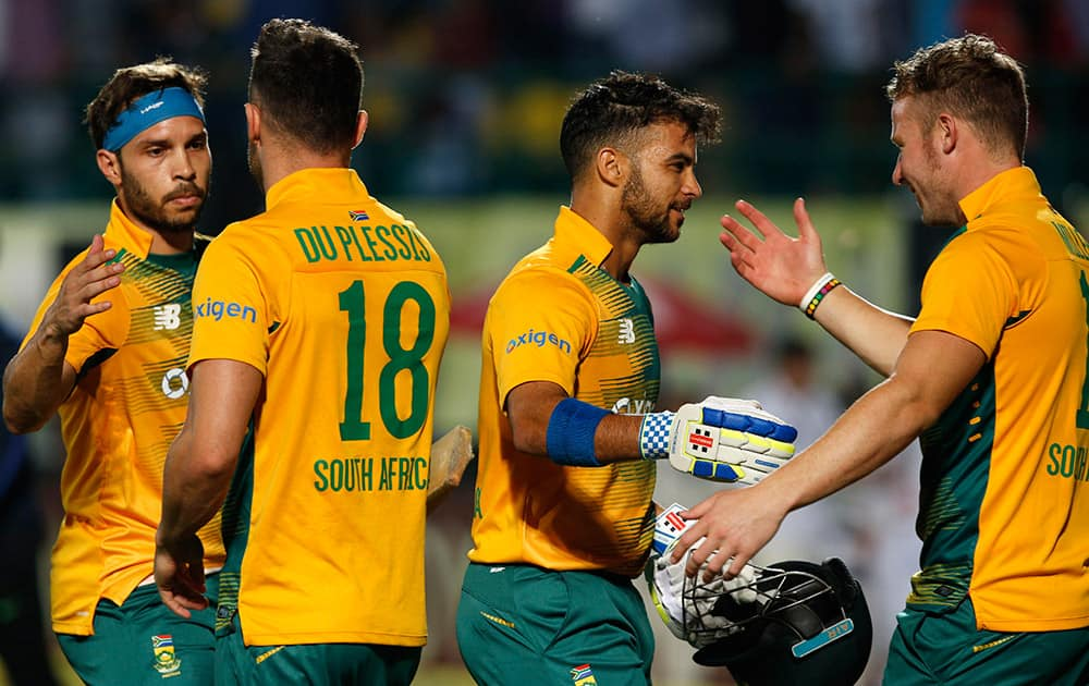 South Africa's Jean-Paul Duminy, second right, celebrates with teammate David Miller as he leaves the ground after winning the first Twenty20 match against India in Dharmsala.