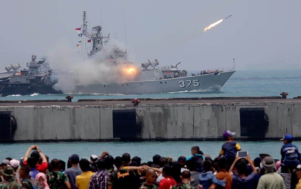 People watch as missiles are launched from an Indonesia military ship for a rehearsal for the upcoming parade held to commemorate the 70th anniversary of the Indonesia Armed Forces in Cilegon, Banten province, Indonesia.