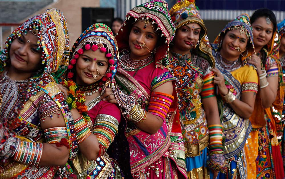 Girls in traditional attire pose for photographs as they practice the Garba, the traditional dance of Gujarat state, ahead of Navratri festival in Ahmadabad.