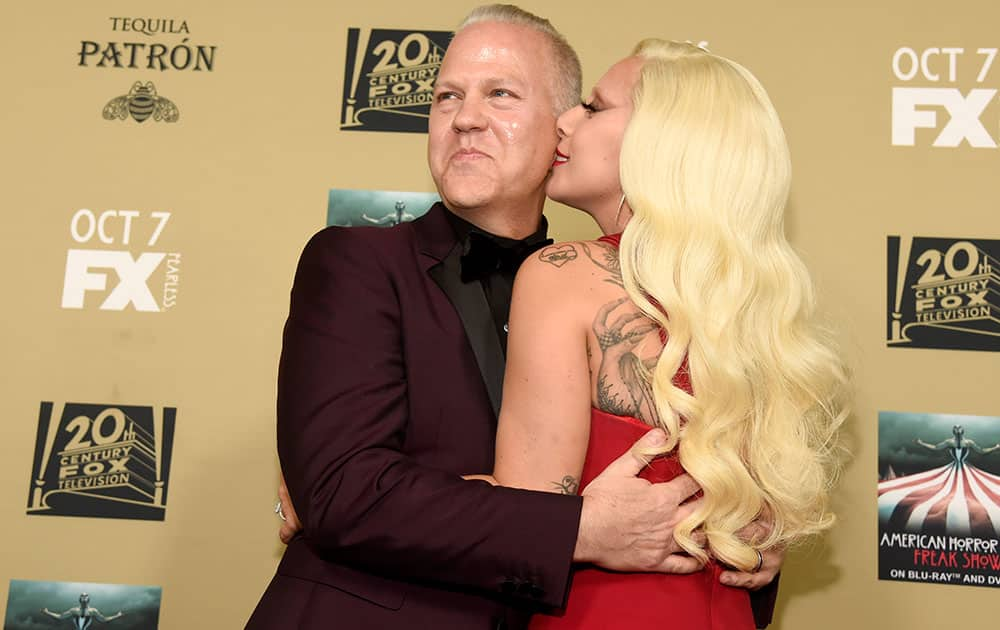 Lady Gaga, right, kisses executive producer/director/writer Ryan Murphy as they arrive at the Los Angeles premiere screening of