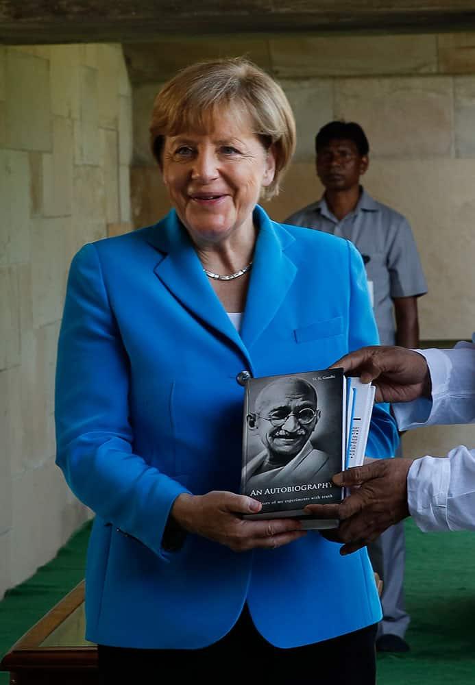 German Chancellor Angela Merkel shows a book of Mahatma Gandhi autobiography, presented to her during her visit to the Mahatma Gandhi memorial, in New Delhi.