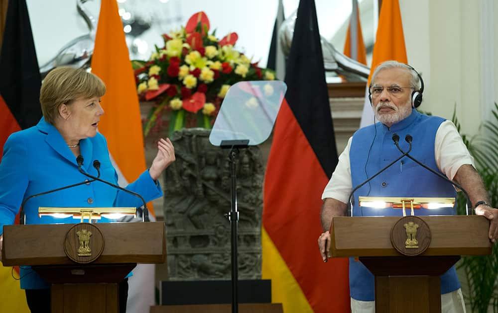 German Chancellor, Angela Merkel, left, and Indian Prime Minister, Narendra Modi, address the media in New Delhi.