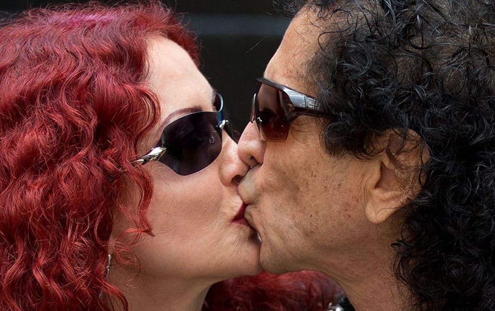 El Tri lead singer Alex Lora, right, kisses his wife and bandmember Chela Lora as they pose for pictures during a press conference to announce the release of the band's new album,