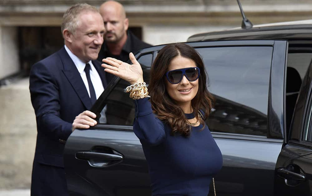 Mexican actress Salma Hayek waves while her husband Francois-Henri Pinault, CEO of luxury group Kering, holds the car door after Stella McCartneys spring-summer 2016 ready-to-wear fashion collection presented during the Paris Fashion Week.