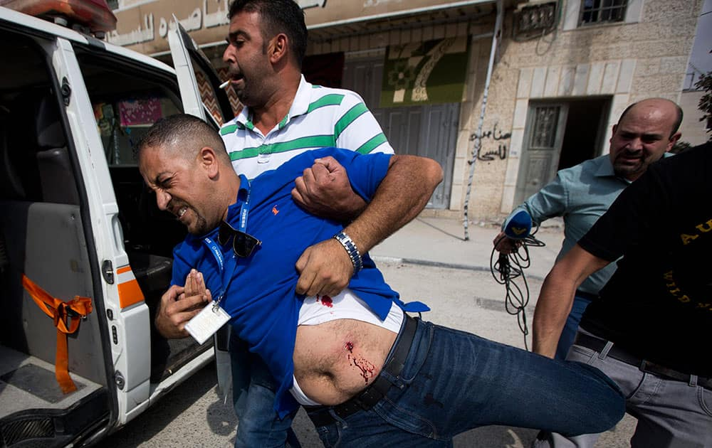 Palestinians carry a TV cameraman Salah Zayed who was shot with live bullets during clashes between Palestinian and Israeli forces at Qalandia checkpoint between Jerusalem and the West Bank city of Ramallah.