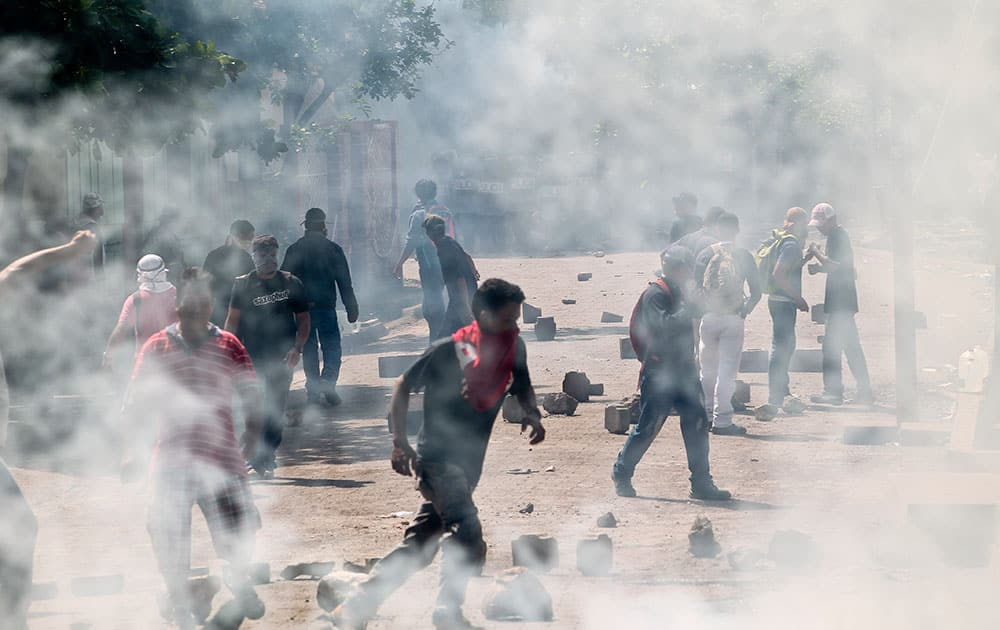 Protesters run in between clouds of tear gas during clashes between striking miners and riot police in El Limon, Nicaragua.