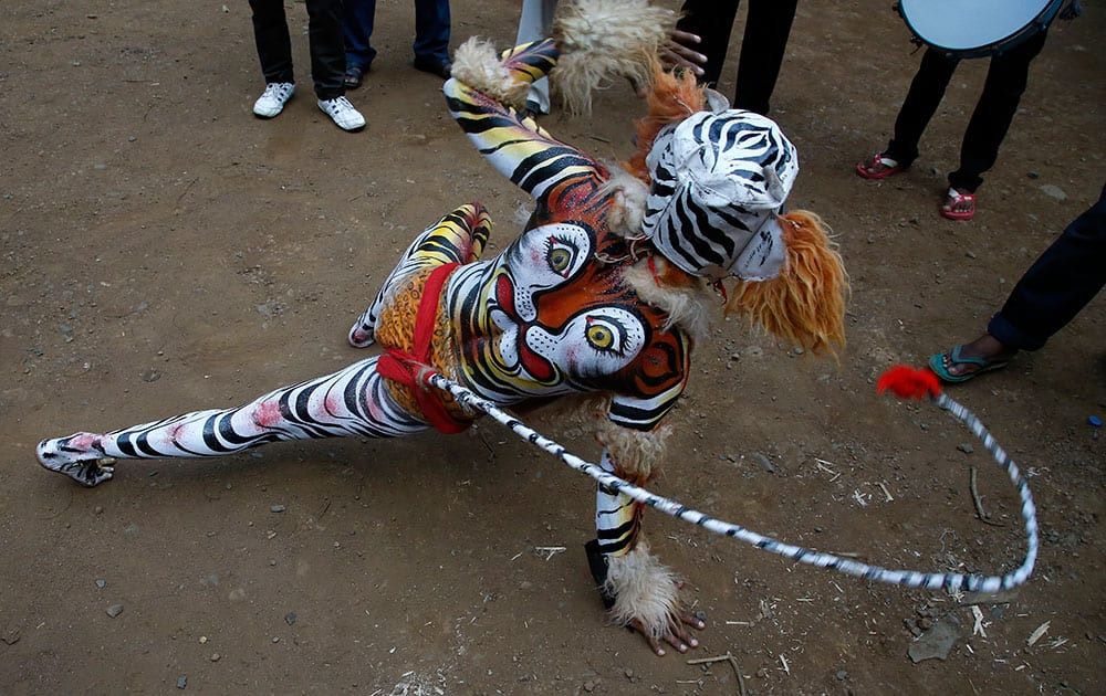 An Indian artist with his body painted with the likeness of a tiger performs to support the save tigers campaign during the Wildlife Week celebrations in Mumbai.