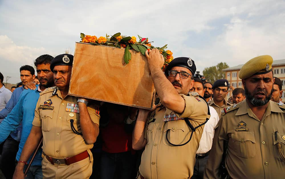 Indian police officers carry the coffin of their colleague Altaf Ahmed during his wreath laying ceremony in Srinagar, Kashmir. Militants gunned down Ahmed in a brief shootout at Gund Dachin area of Bandipora in north Kashmir on Wednesday.