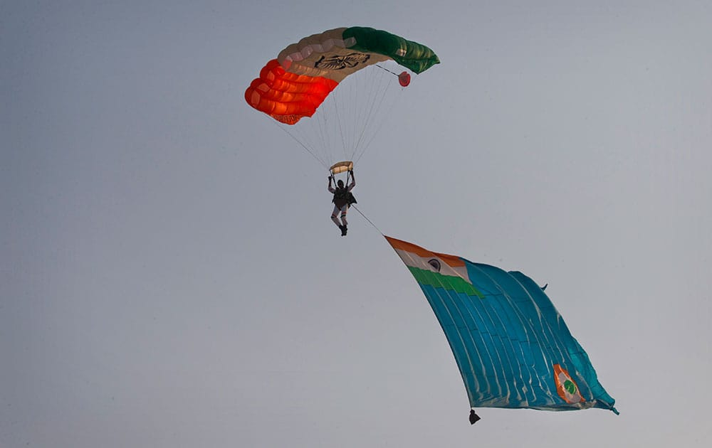 A member of an Indian Air Force (IAF) Akash Ganga sky diving team dives with an IAF flag during Air Force Day parade at Hindon Air Force base near New Delhi.