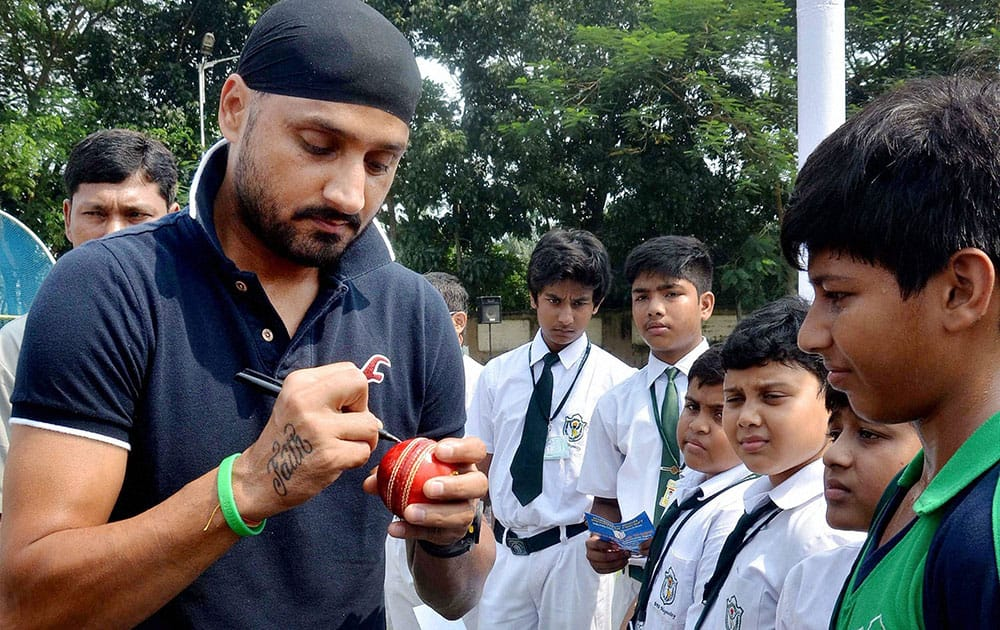 Harbhajan Singh giving autographs on a cricket ball to fan during a programme in North 24 Pargana district of West Bengal.