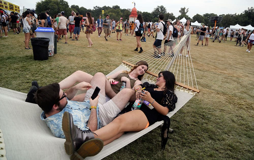 Chaz Mang, Victoria Kissinger and Victoria Jones share a hammock at the Austin City Limits Music Festival in Zilker Park, in Austin, Texas.