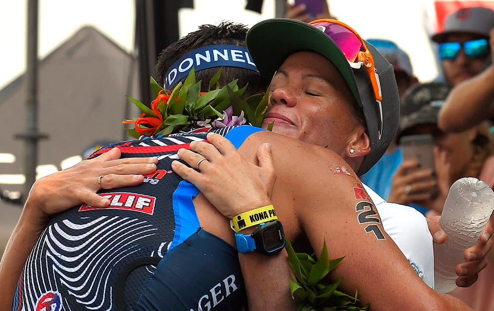 Timothy O'Donnell, left, hugs his wife and fellow competitor, Mirinda Carfrae, of Australia, after taking third in the men's portion of the Ironman World Championship triathlon in Kailua-Kona, Hawaii.