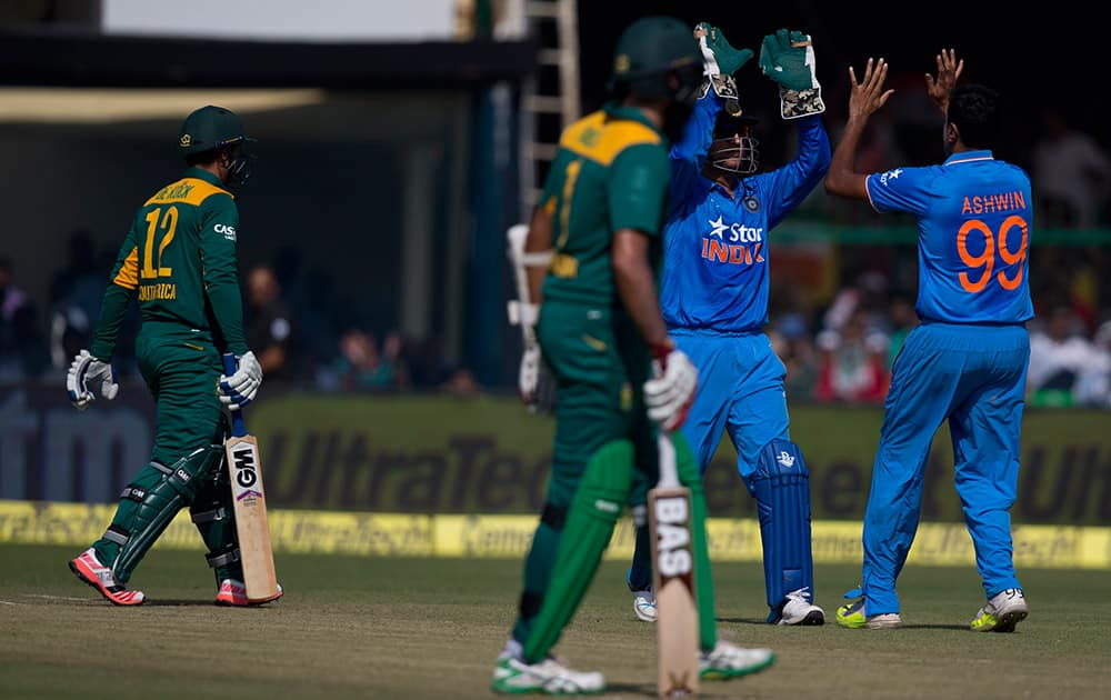 Indian players, Ravichandran Ashwin, right, and Mahendra Singh Dhoni, second right, celebrate as South African batsman Quinton de Kock, left, is caught at the slips during the first of their five one-day match series in Kanpur, India.