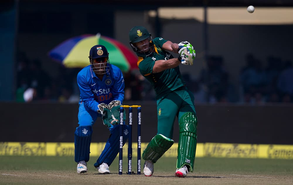 As Indian wicketkeeper Mahendra Singh Dhoni watches, South African batsman A B de Villiers hits a six while playing against India in the first of their five one-day match series in Kanpur, India.