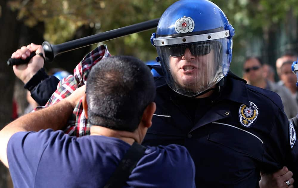Turkish police officers in riot gear disperse protesters that tried to reach the site of Saturday's explosions to hold a memorial for the victims, in Ankara, Turkey.