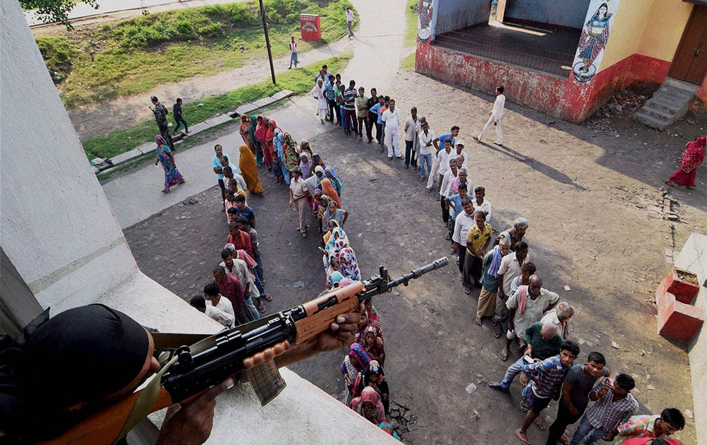 A security person keeps vigil as voters wait in queues to cast votes at a polling station during Bihar assembly elections in Begusarai.