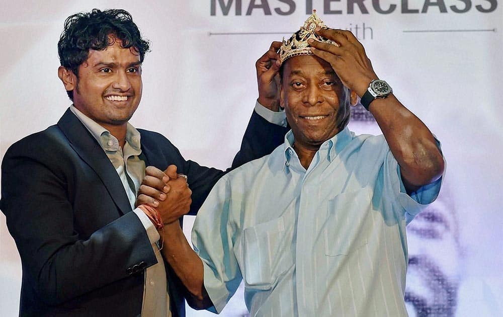 Indian footballer Dipendu Biswas presents a crown to legendary Brazilian footballer Pele during a promotional event in Kolkata.