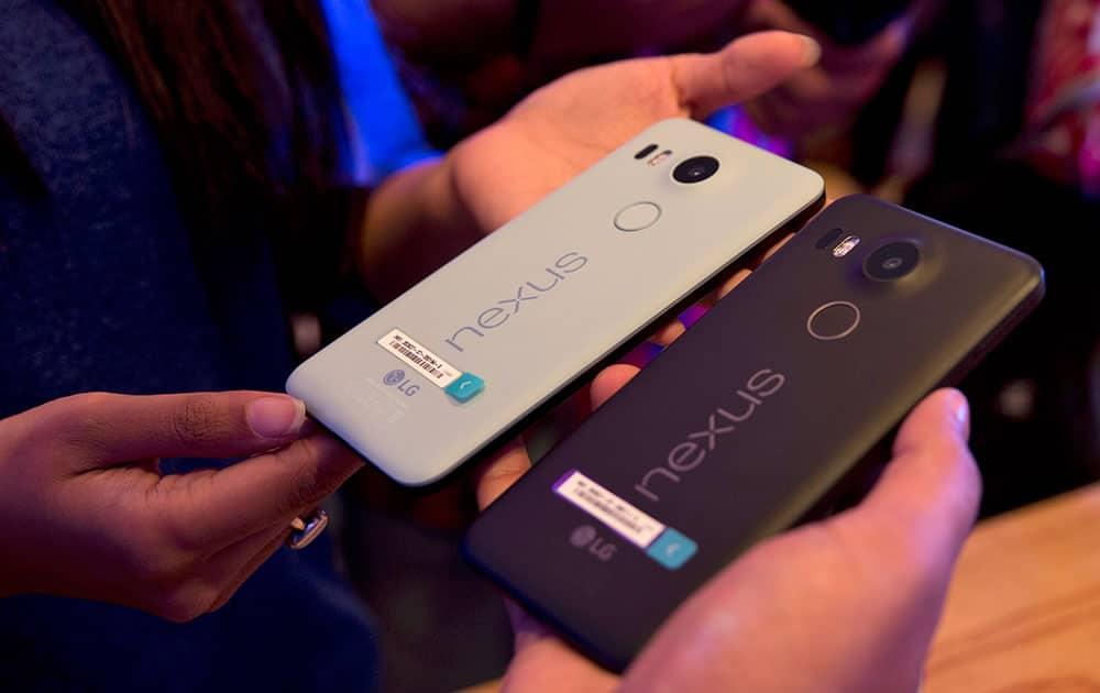 People hold the new Google Nexus phones during the launch of its latest range of Nexus 5X and Nexus 6P in New Delhi.