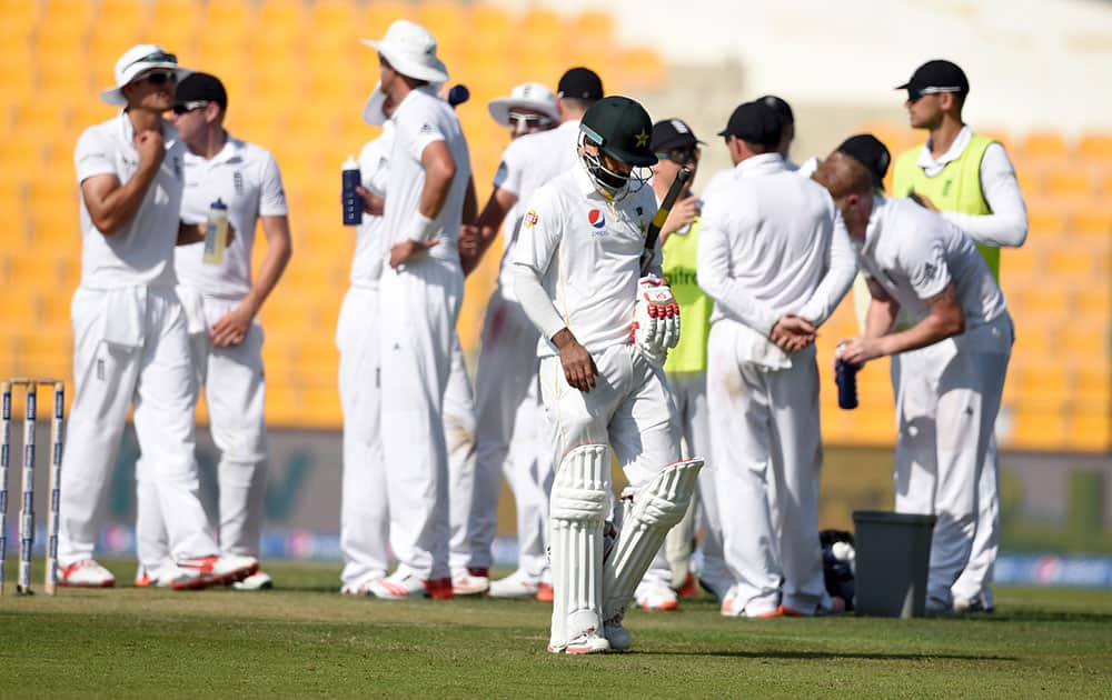 Pakistan batsman Muhammed Hafeez walks back for 98, after being dismissed by England's Ben Strokes, during the first day of the first test match between England and Pakistan at the Zayed Cricket Stadium in Abu Dhabi, United Arab Emirates.