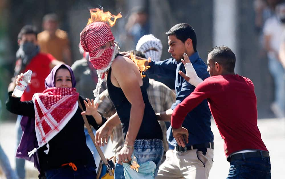 Palestinian's try to help a demonstrator who accidentally set his scarf on fire during clashes with Israeli troops in the West Bank city of Hebron.