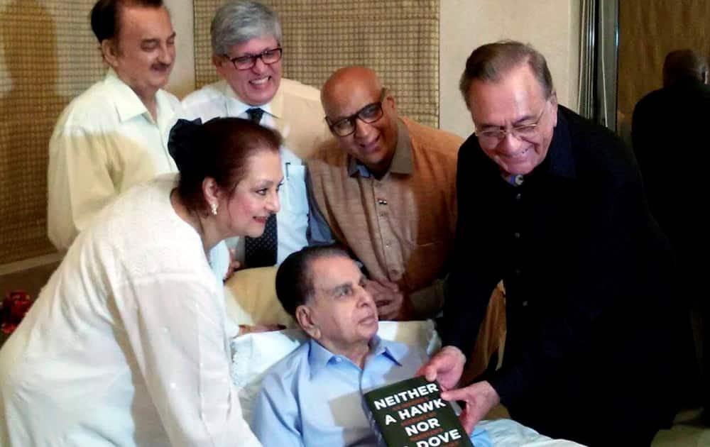 Former foreign minister of Pakistan Khurshid Mahmud Kasuri presents his book to bollywood veteran actor Dilip Kumar and his wife Saira Banu at the actors residence in Mumbai.