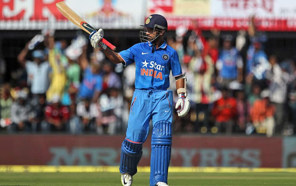 Ajinkya Rahane raises a bat after scoring 50 runs against South Africa during their second one day international cricket match between them in Indore.