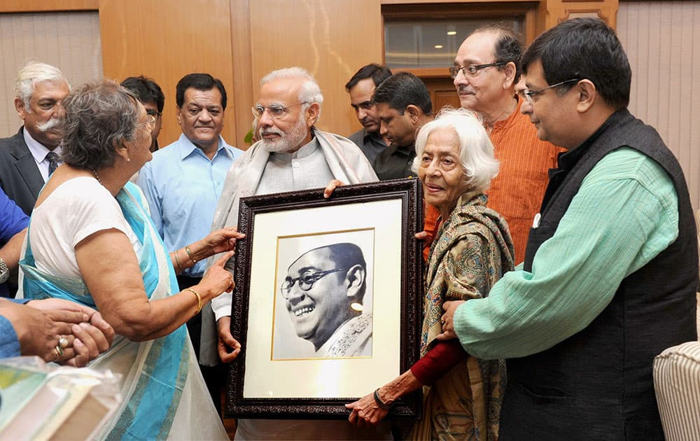 Prime Minister Narendra Modi being presented a portrait of Netaji by the family members of Netaji Subhas Chandra Bose, at 7, Race Course Road, in New Delhi.