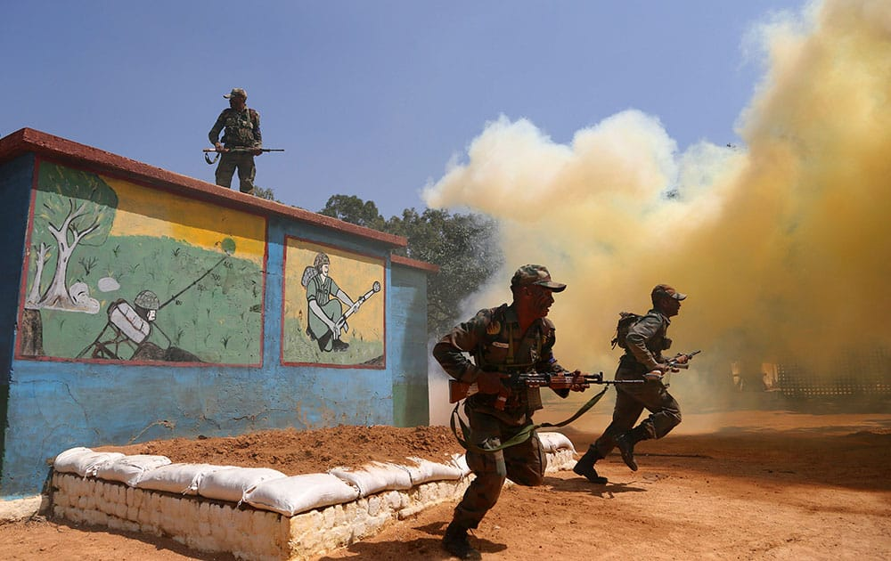 Indian army soldiers run after clearing an obstacle amid smoke from canisters to showcase their skills during a training session at army's Madras Engineer Group training centre in Bangalore, India.