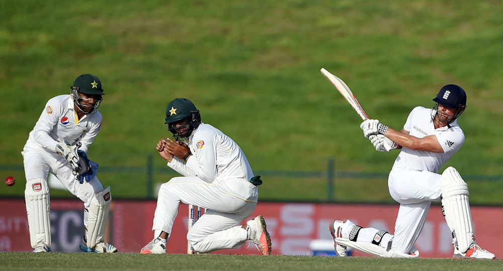 England captain Alastair Cook, right, hits a ball as Pakistan's Shan Masood protects himself during the third day of first test match between England and Pakistan at Zayed Cricket Stadium in Abu Dhabi, United Arab Emirates.