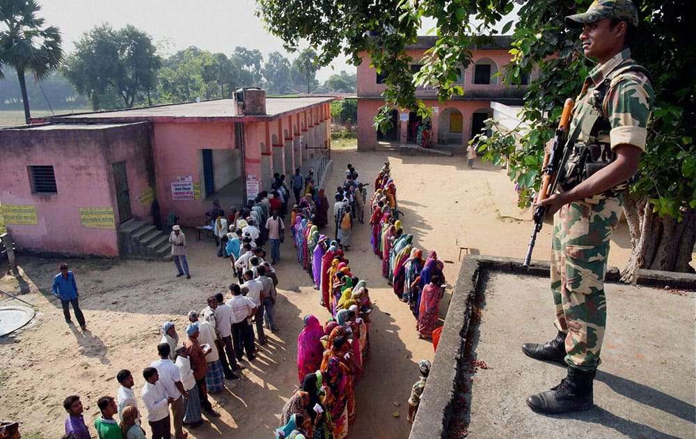 Voters wait in queue to cast their vote during second phase of Bihar elections at Gaya.