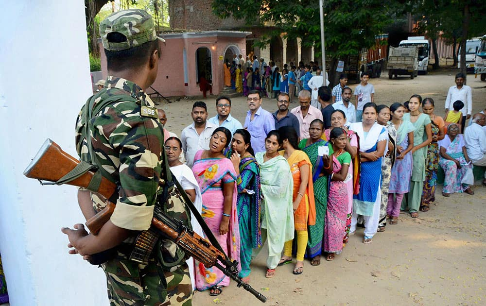 Voters wait in queues to cast their vote during second phase of Bihar elections at Gaya.