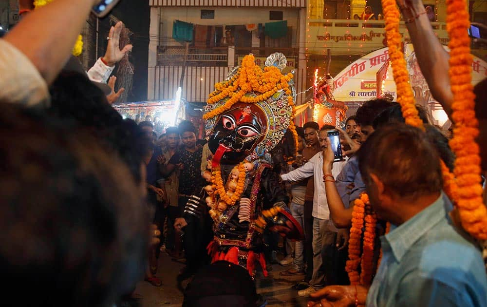 An Indian man dressed as Hindu Goddess Kali dances in a street play ahead of Dussehra festival in Allahabad.
