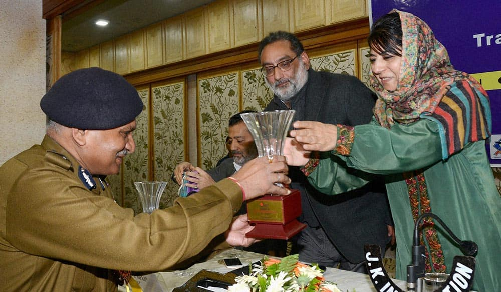 Director General of Jammu and Kashmir police K Rajindra presents a momento to Member Parliament and president of ruling party, PDP, Mehbooba Mufti as state Finance Minister Haseeb Drabu looks on during the inauguration of one day seminar on Isla-Traffic Management in J&K.