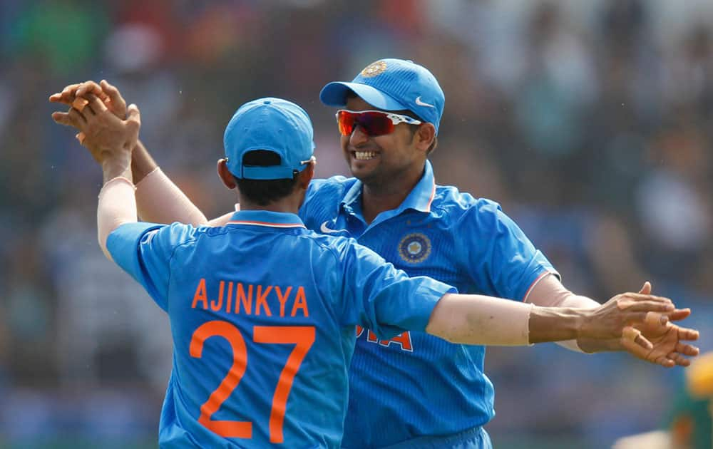 Ajinkya Rahane celebrates with teammate Suresh Raina after he took a catch to dismiss South Africa's David Miller during their third one-day international cricket match in Rajkot.