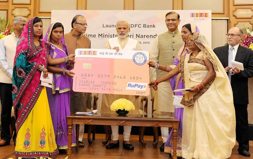 Prime Minister Narendra Modi distributing RuPay Cards under PMJDY by the IDFC Bank to the beneficiaries, at the launch of the IDFC Bank, in New Delhi. Union Minister for Finance, Corporate Affairs and Information & Broadcasting, Arun Jaitley and Minister of State for Finance, Jayant Sinha are also seen.