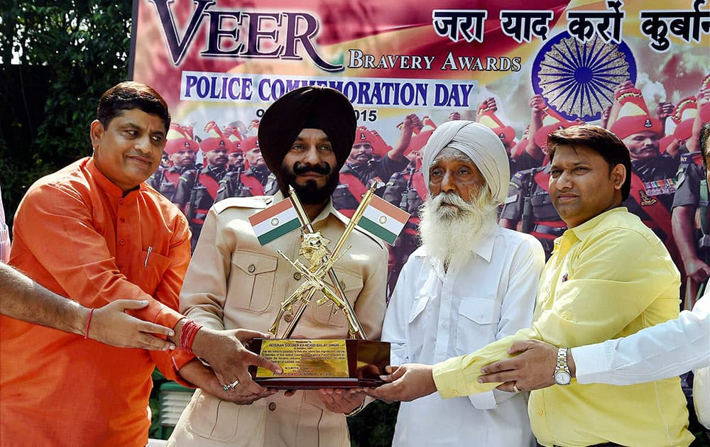 All-India Anti-Terrorist Front chairman M S Bitta presents Veer Bravery Award to Baljit Singh, a CRPF man who fought during Chinese aggression in 1959, in New Delhi.
