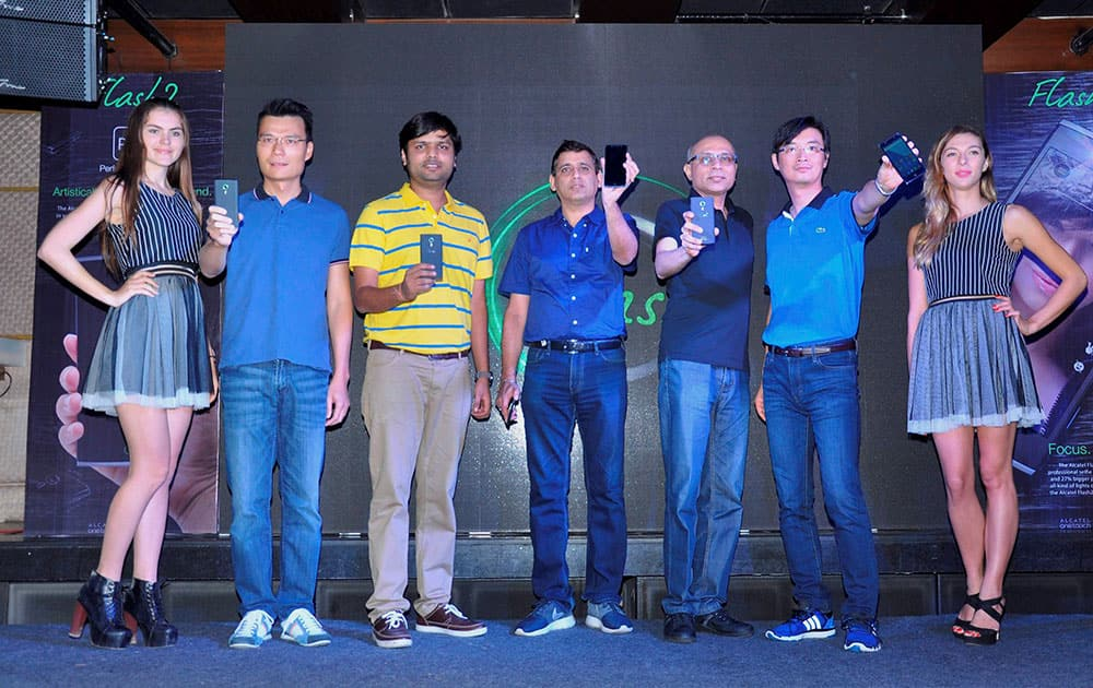 ALCATEL officials along with models displaying new ALCATEL FLASH 2 smartphone during the launch at F-Bar & Lounge in New Delhi.