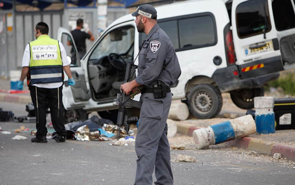 An Israeli policeman stands guard by the body of a Palestinian outside his car at Gush Etzion junction in the West Bank near Jerusalem. Israeli police said a Palestinian drove his vehicle into a group of Israelis and was shot and killed after the attack that injured two people.
