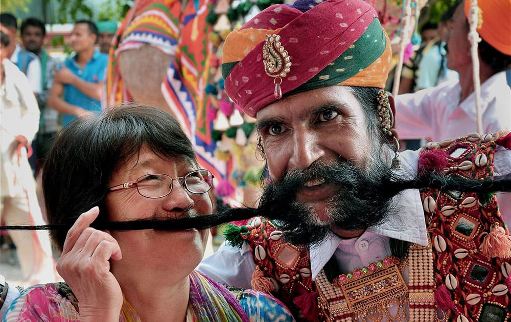 A Rajasthani artist showing his long moustache to entertain tourists welcoming them for seasons first trip of Maharaja Express train in Bikaner.