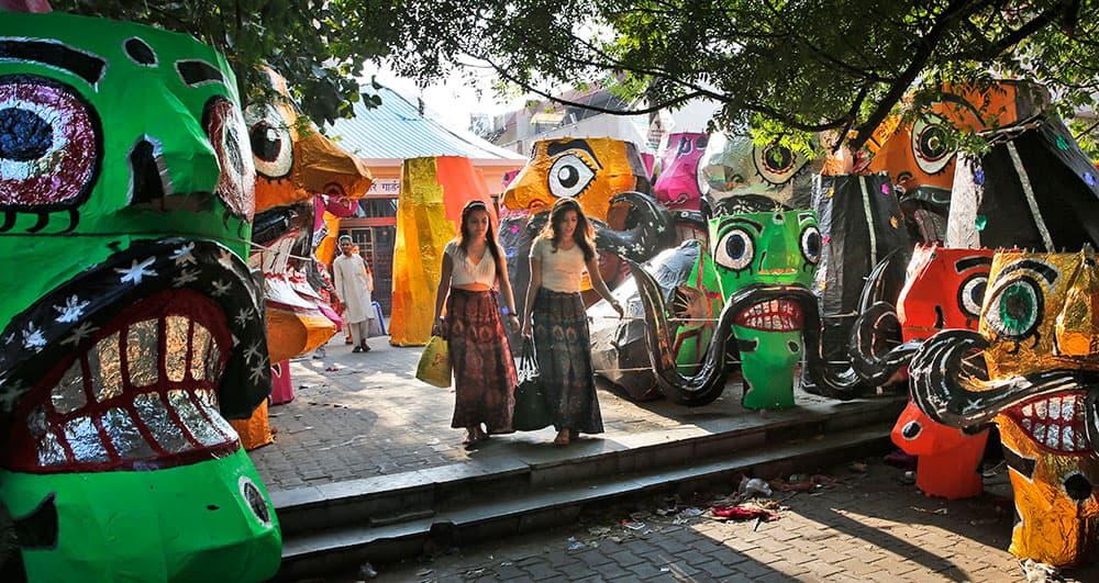 Girls walk past effigies of demon king Ravana displayed for sale at a roadside ahead of Hindu festival Dussehra in New Delhi.