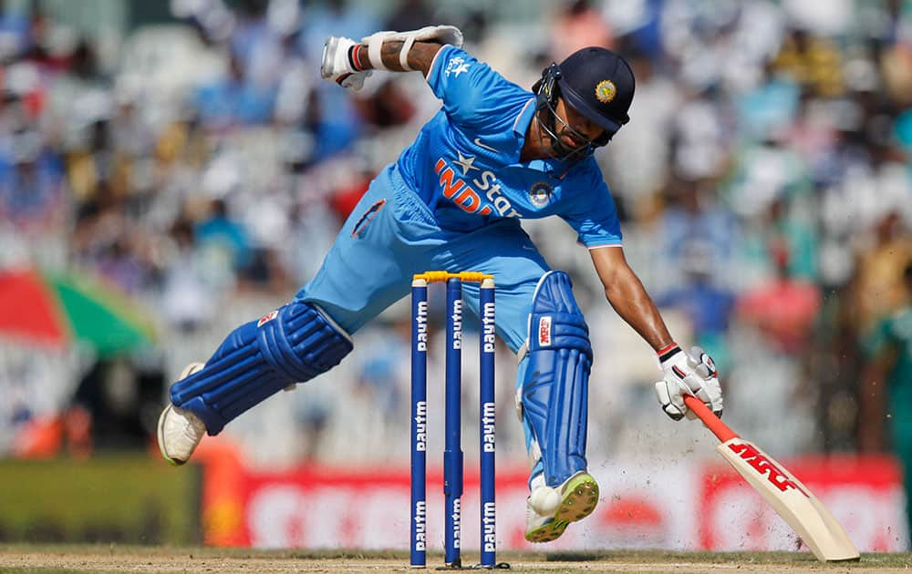 Shikhar Dhawan scores a run during their fourth one-day international cricket match against South Africa in Chennai.