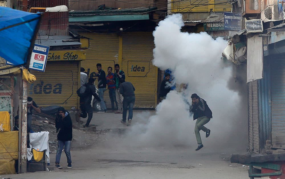 Kashmiri Shiite Muslim jumps to dodge a teargas shell exploding during a religious procession defying restrictions in Srinagar.