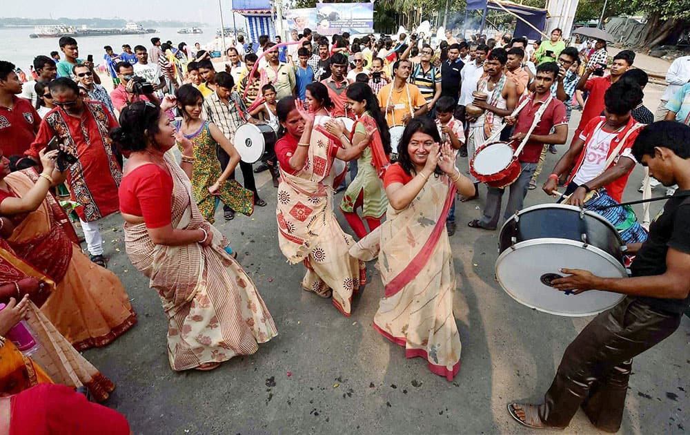 Devotees dancing during immersion of an idol of Goddess Durga, on the bank of river Ganga in Kolkata.