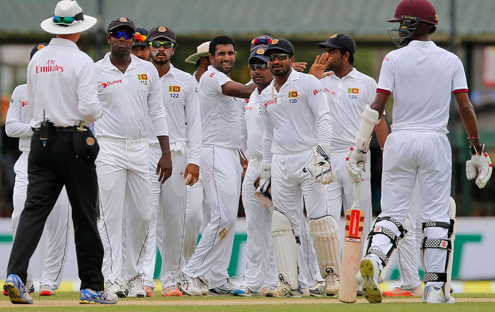 Sri Lanka's cricket team members congratulate Dhammika Prasad, center, for the dismissal of West Indies' Darren Bravo on the second day of their second test cricket match in Colombo, Sri Lanka.