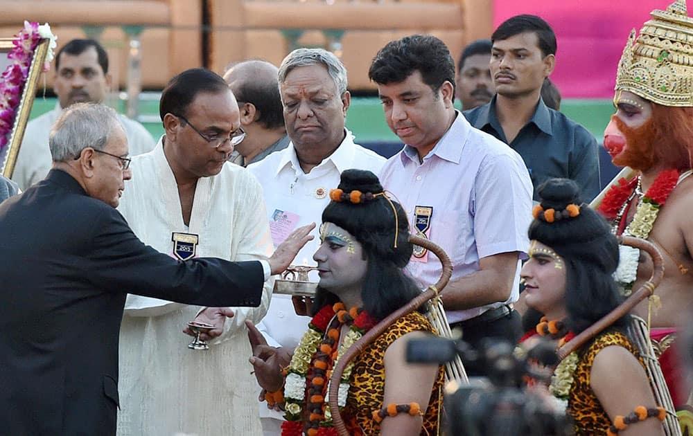 President Pranab Mukherjee performing aarti of artists enacting Lord Ram and Lakshman during Dussehra celebrations at Parade Ground in New Delhi.