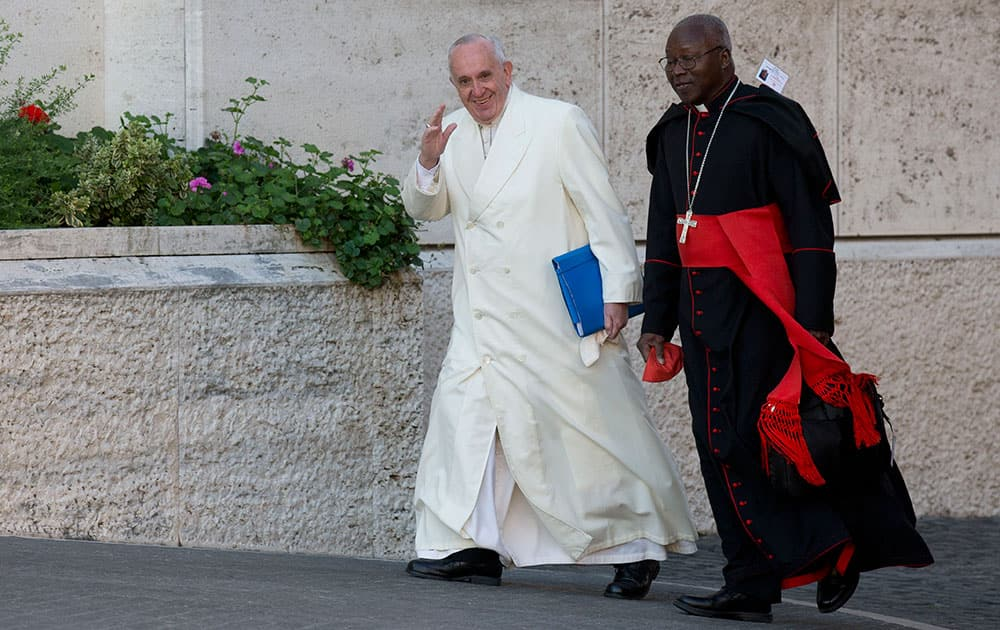 Pope Francis arrives with Cardinal Philippe Nakellentuba Ouedraogo to attend the morning session of the Synod of bishops at the Vatican.